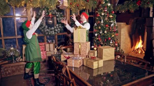 Šťastní elfové s mnoha dárky uvnitř. Vánoční zdobený pokoj a elfové v zelených kostýmech kladou na stůl zabalené dárky. Vánoční čas.