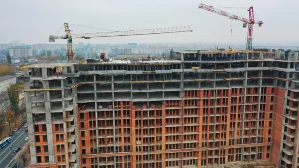 construction of a residential apartment complex. Multi-storey building under construction. Building cranes are working. Aerial view.