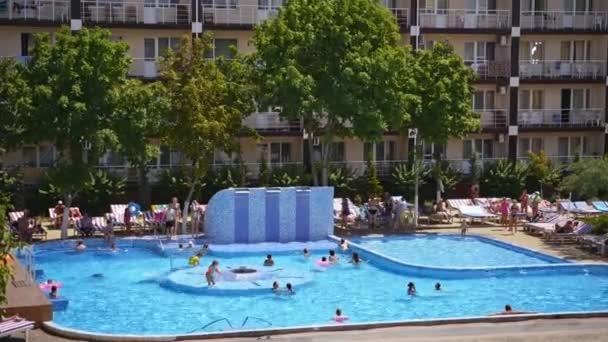 Bazén venku. Mnoho lidí plave v modré vodě bazénu za slunečného dne. Bazén na hotelovém zázemí v létě.