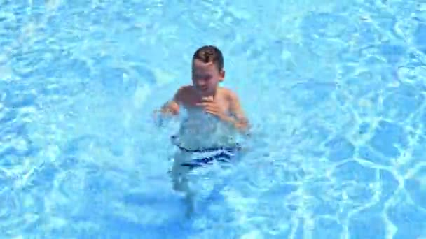 Happy boy swimming outdoors. Cute boy in blue clear water of the swimming pool. Child having joyful time in outdoor water park in summer.