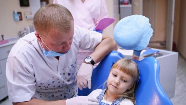 Šťastné dítě v zubním křesle. Muž zubař si před ošetřením zubů promluví s malou holkou. Usmívající se dítě v kanceláři stomatologa.