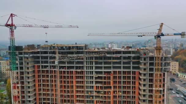 New construction in the city center. Wide high-rise building under construction outdoors. Aerial view. Camera moving around.
