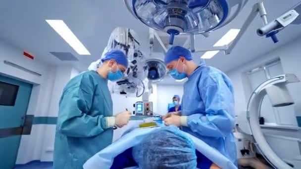 Blick von der Seite auf erfahrene Chirurgen mit medizinischen Werkzeugen während der Operation. Gesundheitskonzept.