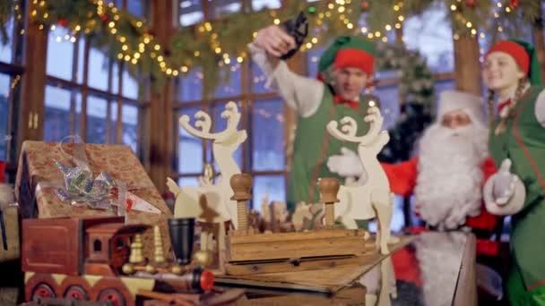 Dřevěné ručně vyráběné hračky na stole. Santa Claus a dva elfové s dárky na vánoční pozadí uvnitř.