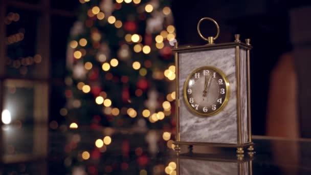 Pěkné hodiny na rozmazané vánoční pozadí. Hodiny ukazují půlnoc. Je dvanáct hodin. Šťastný nový rok. Vánoční koncept