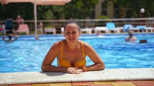 Woman enjoys the time near the pool. Healthy female in yellow swimsuit is relaxing in the swimming pool in the water park. Summer vacation.