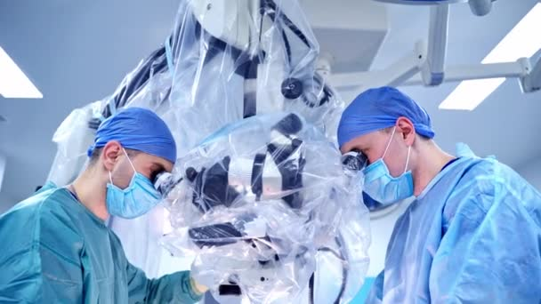 Spezialisten schauen durchs Mikroskop. Chirurgen in medizinischer Uniform führen die Operation und den Einsatz moderner Geräte in der Klinik durch. Neue Technologien in der Medizin.