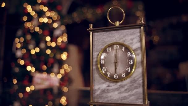 Arany óra homályos karácsonyi háttérrel. Az óra hat órát mutat. A használt kéz egy mechanikus óra körforgásában mozog. Újévi ünnep. Karácsonyi koncepció.