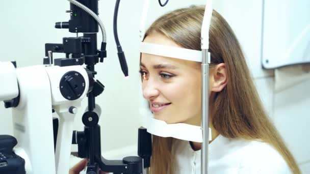 Young woman checking her eyes in clinic. Biomicroscopy device. Doctor examining eye structure of a female patient with the help of modern medical equipment. Professional health care.