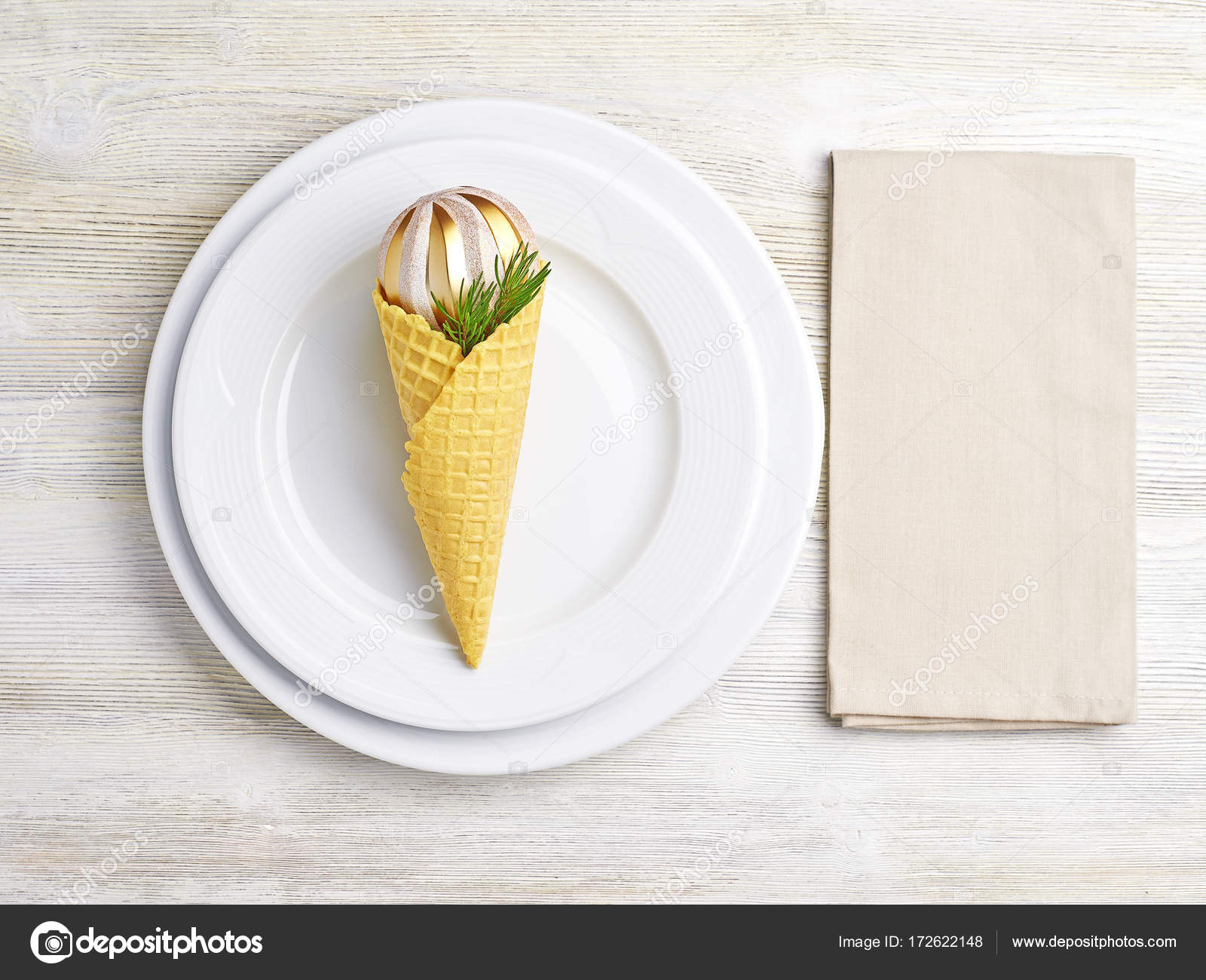 Christmas table setting. Plates, napkin and ice cream cone with ...