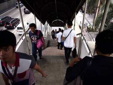 People climbing up and down a staircase of an overpass bridge leading to an MRT station.