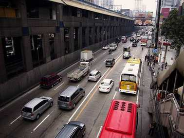 Private and public vehicles passing along EDSA and the Boni MRT Station in Mandaluyong City, Philippines.