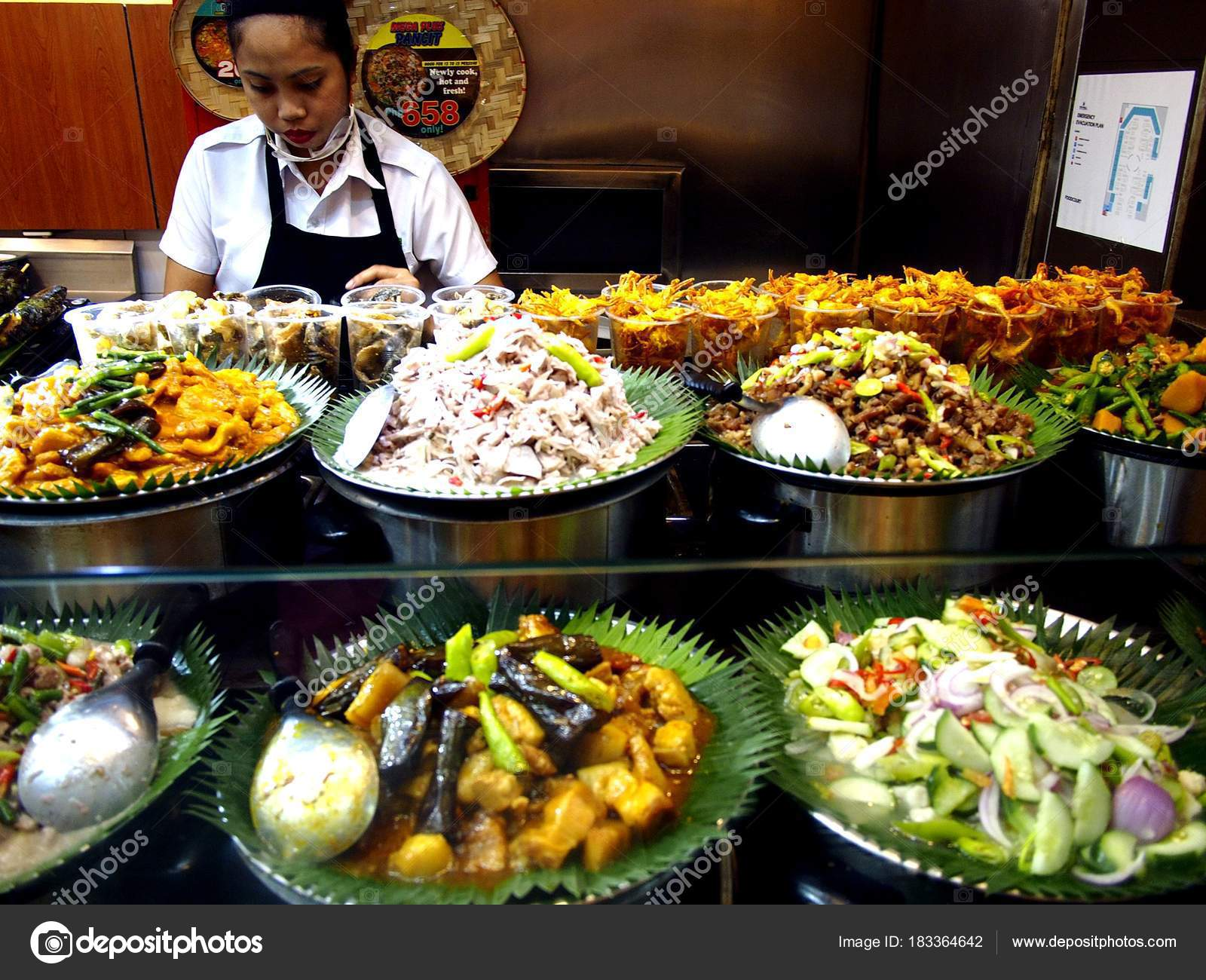 Assorted Filipino dishes on display at a food kiosk in a