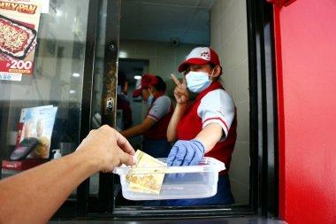 Antipolo Şehri, Filipinler - 5 Mayıs 2020: Bir fast food restoranının çalışanı, Covid 19 virüs salgını sırasında vitrindeki bir müşteriden ödeme aldı.