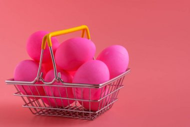Shopping cart with Easter eggs on pink background. Easter shopping and sale, copy space