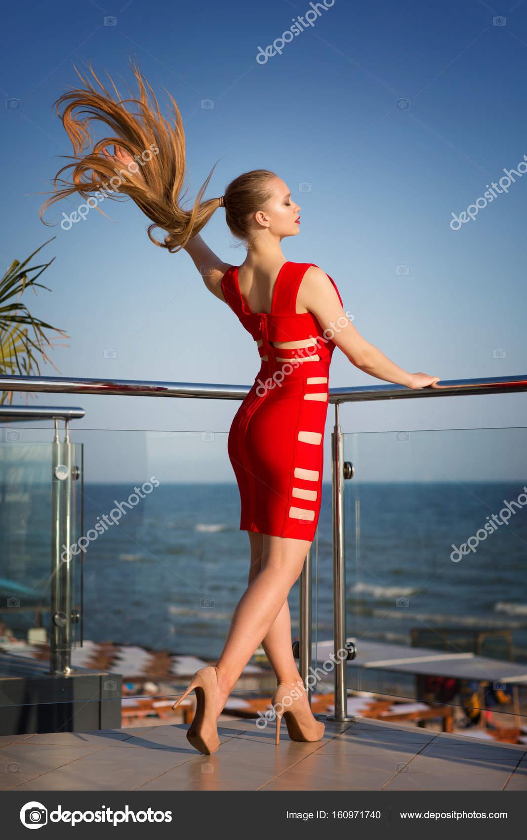 9b662bb2c1a Une fille chaude avec des cheveux fantastique sur un fond naturel. Une dame  élégante sur une terrasse en été. Une jeune fille vêtue d une robe rouge ...