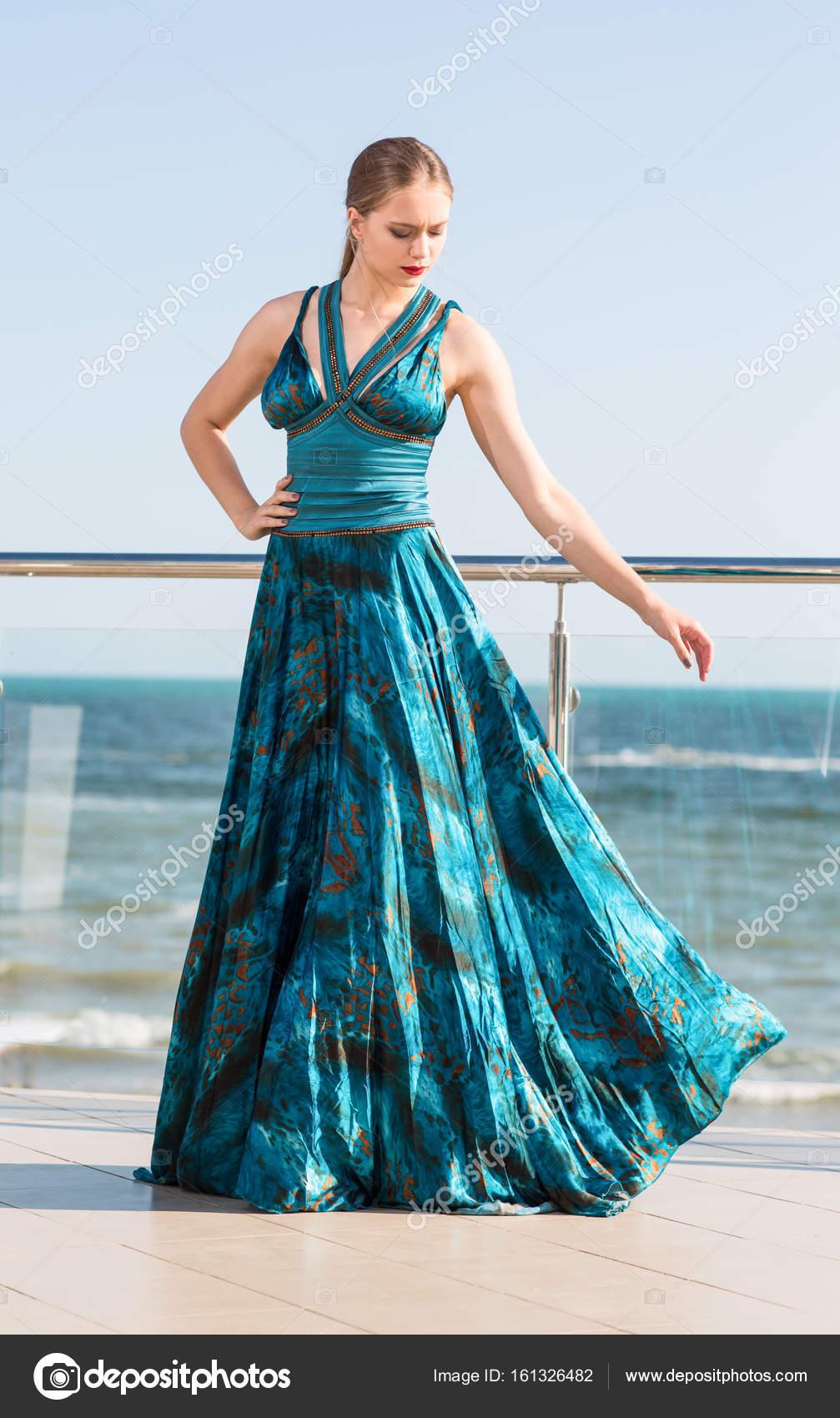 Eine modische Frau in einem wunderschönen smaragdgrünen Kleid auf ...