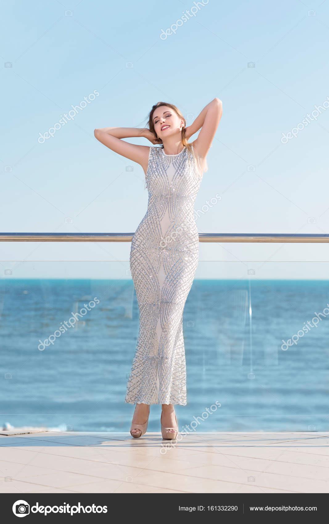 b7954c93a3f Une femme séduisante dans une fantastique robe blanche sur un fond bleu vif  de la mer ...