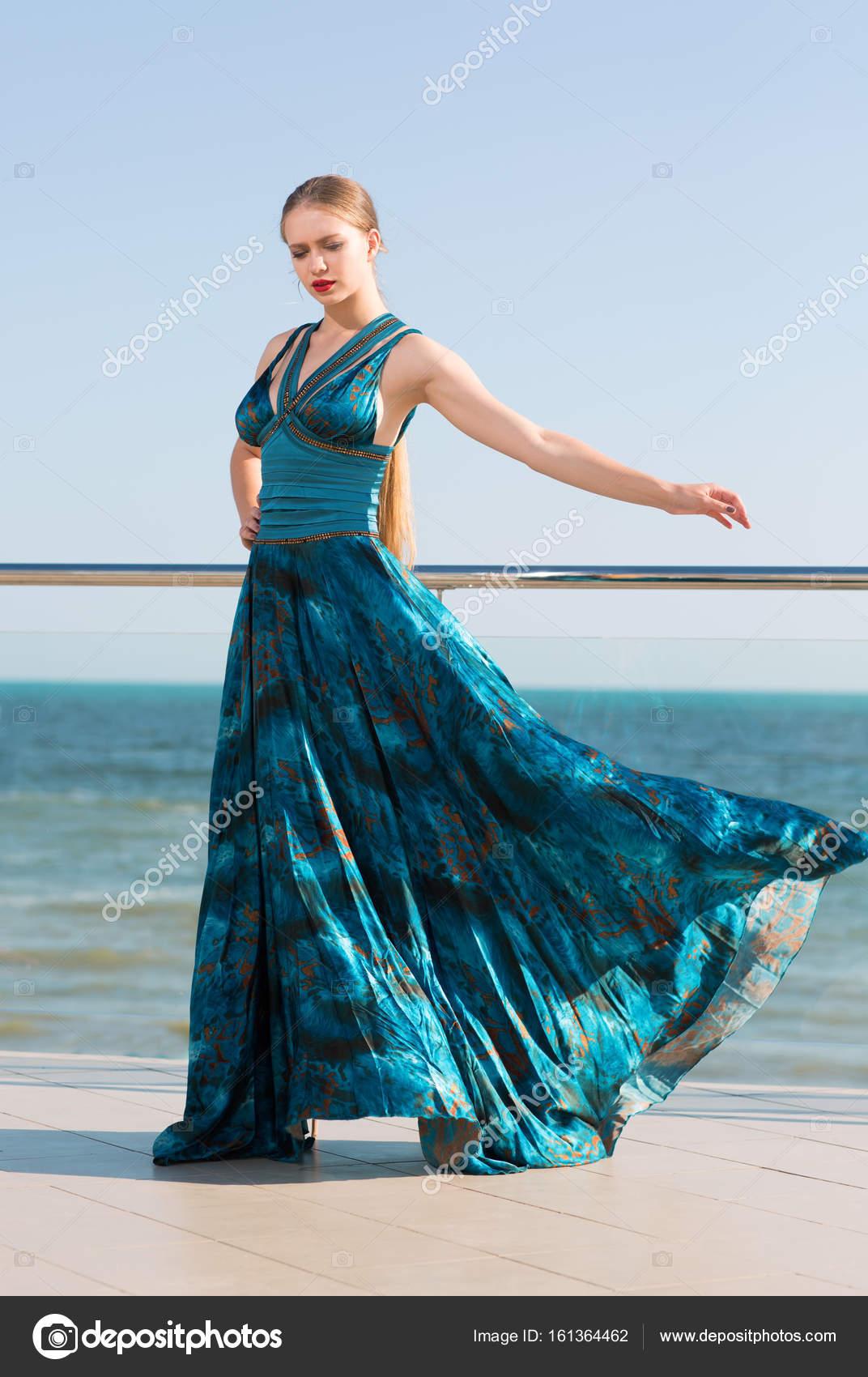 edcd8b2a8231 Una signora elegante con coda di cavallo bionda e in un abito verde  smeraldo lungo ondeggiante
