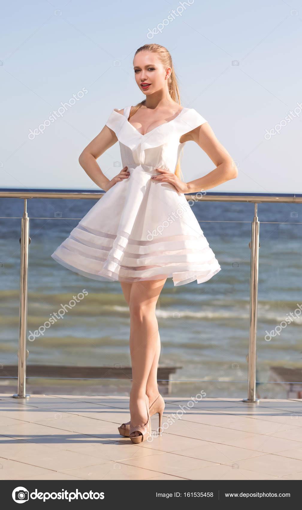 Eine gut aussehende Dame in einem fantastischen weißen Kleid auf ...