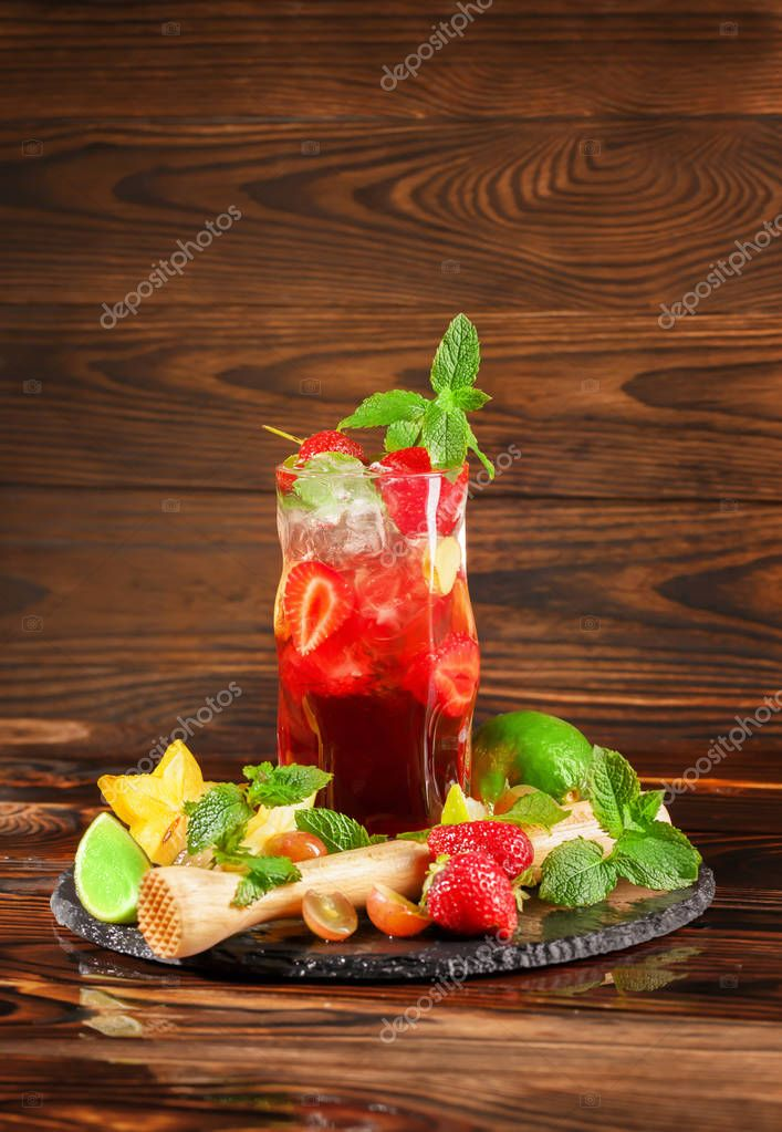 Summer fresh alcohol beverage with sweet strawberries, juicy lime, mint, and wine on a wooden background. Many exotic fruits near the cocktail. Copy space.