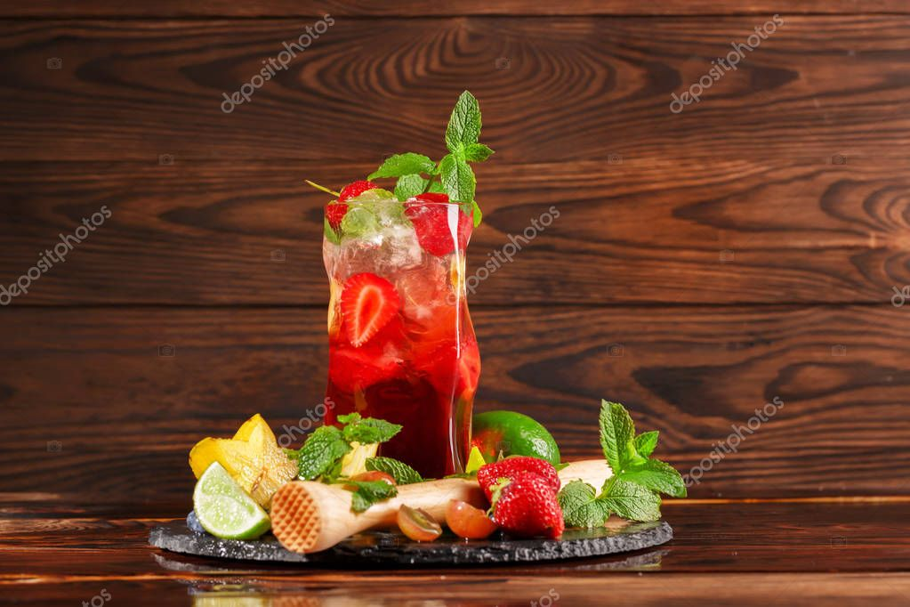 A summer alcohol bright red beverage with berries, lime, mint, and vermouth on a brown wooden background. Many delicious, fresh and exotic fruits near the cocktail. Copy space.