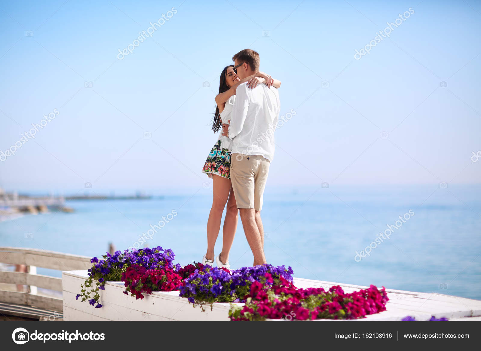 Happy girlfriend and boyfriend hugging near pink and purple flowers. Lovers on a sea beach. Tourism and luxurious lifestyle concept. Copy space.