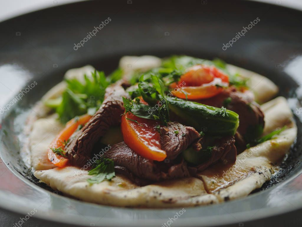 Close-up of a restaurant dish. Served cafe lunch on a blurred background. Grilled vegetables and meat steak on a bread.