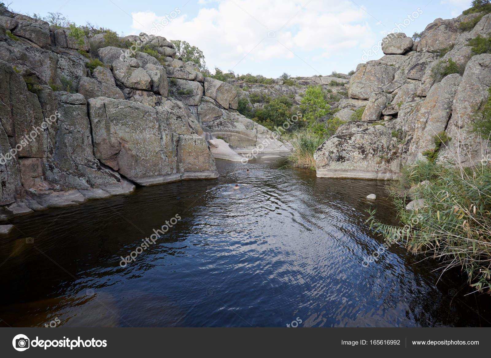 Two men swimming in a beautiful lake in abandoned granite