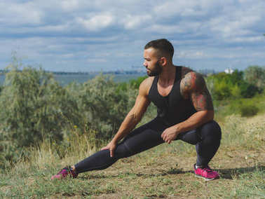 Full-length photo of a handsome, strong male stretching on a grass and on a natural background. Workout in the outdoors.