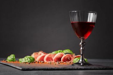 A thinly sliced balyk and a glass of red wine on the saturated black background. Dry red wine, traditional Italian snacks, basil and peppercorns on the table. Copy space.