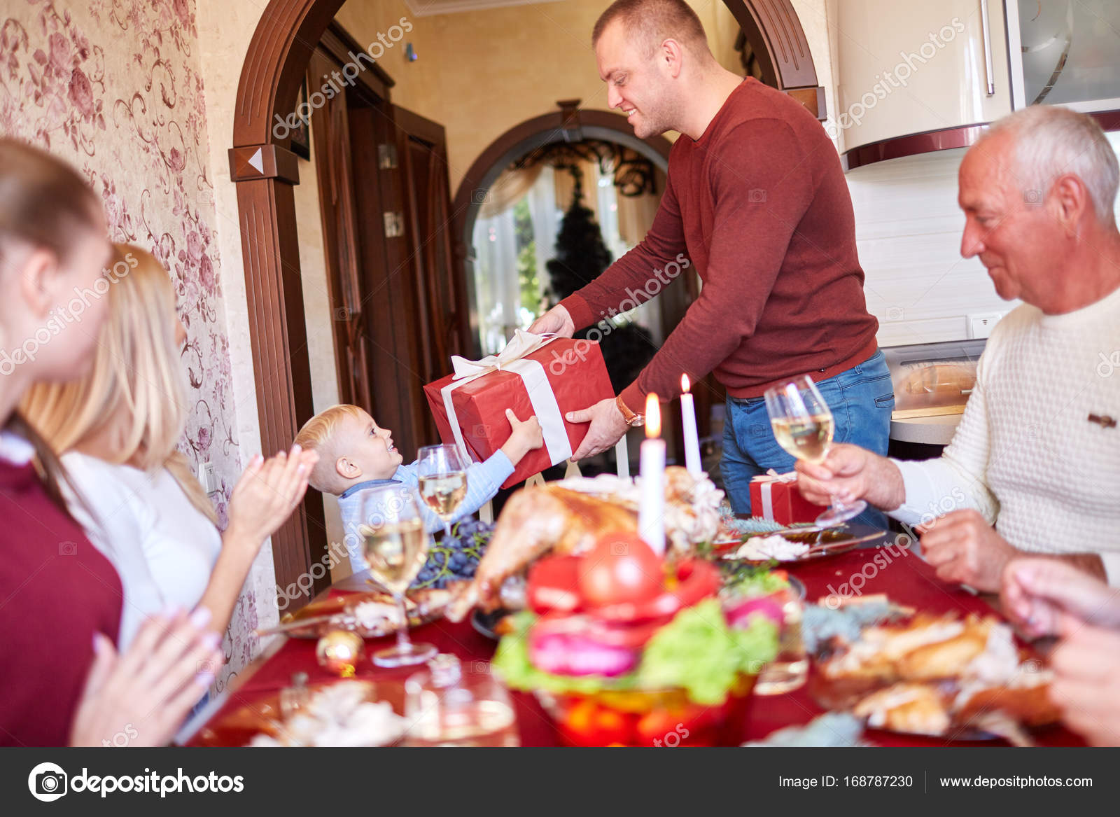 Dad giving a red gift to little son on a festivebackground. Family Christmas presents concept.– stock image