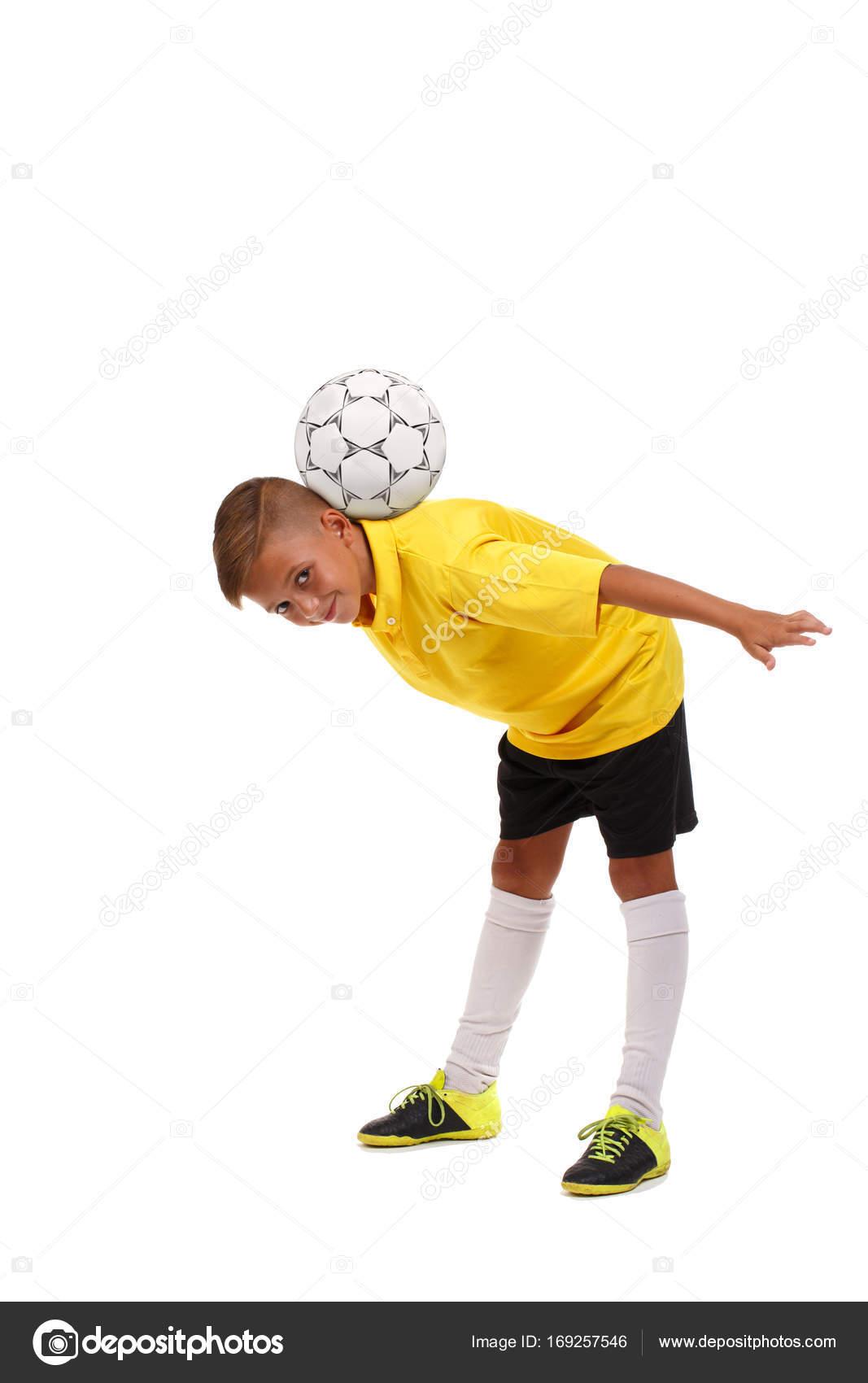 aa9ffdabdb Criança se divertindo com uma bola. Jogador de futebol jovem isolado em um  fundo branco