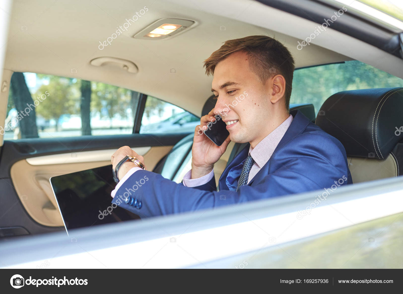 businessman looking at the clock in his car with a laptop talking on