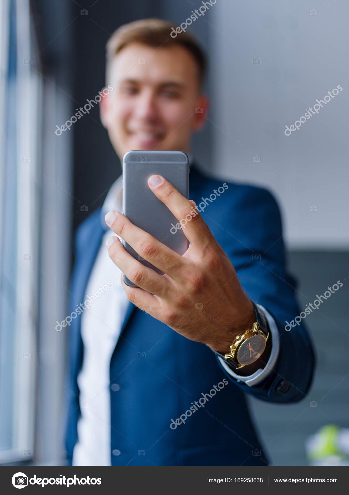 Primo Piano Di Un Lavoratore Di Ufficio Che Tiene Un Telefono Su Uno
