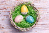 Photo top view of colorful Easter eggs with green grass in wicker basket on wooden background. Easter concept.