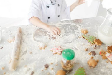 female baking cookies, preparation for baking. Flour with dough, eggs, eggshells, and biscuits on the kitchen table.