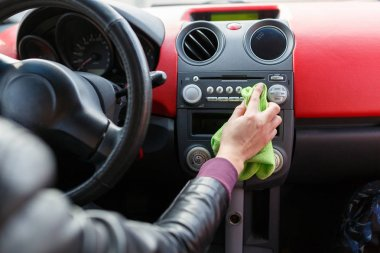 A young woman wipes the dust with a green rag in the car. Dry cleaning of the car panel, car washing.Woman cleaning car dashboard.