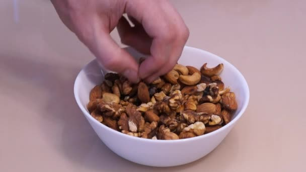 Ořechy smíchat. Kešu. Vlašský ořech. Almond. Muž ruce si mandle. Různé druhy ořechů