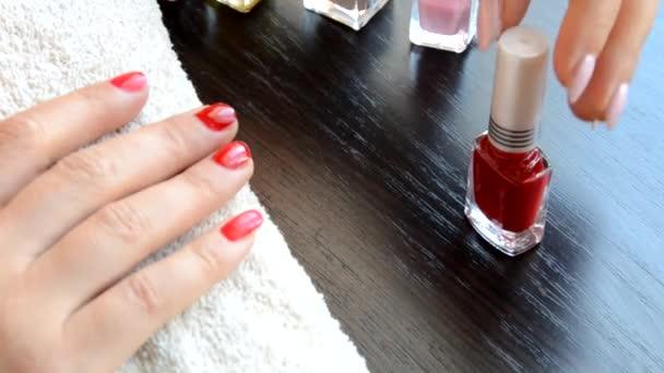 Maniküre - Schöne gepflegte Damennägel mit rotem Nagellack auf weichem weißen Handtuch. Rot- und Perlglanzlack, wählt Nagel
