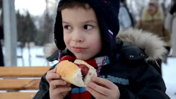 Chlapec pojídající hot dog venku v zimě