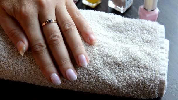 Manikúra - krásné manikúra ženské nehty s červeným lakem na nehty na měkkém bílém ručníku. červený a perleťový lak, vybírá nehty
