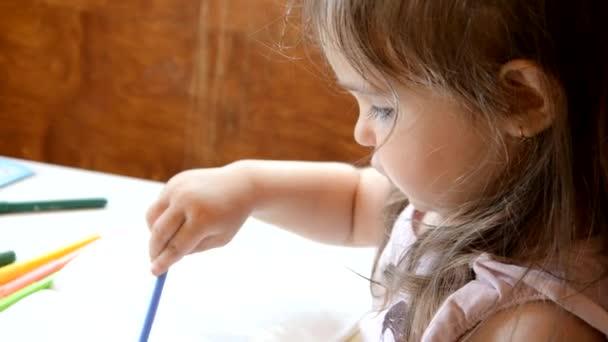 Két három éves kislány filctollal díszíti az állatokat. A gyerek házi feladatot csinál és esszét ír. Általános iskolai vagy általános iskolai osztály. A kezek és színes ceruzák közelsége.