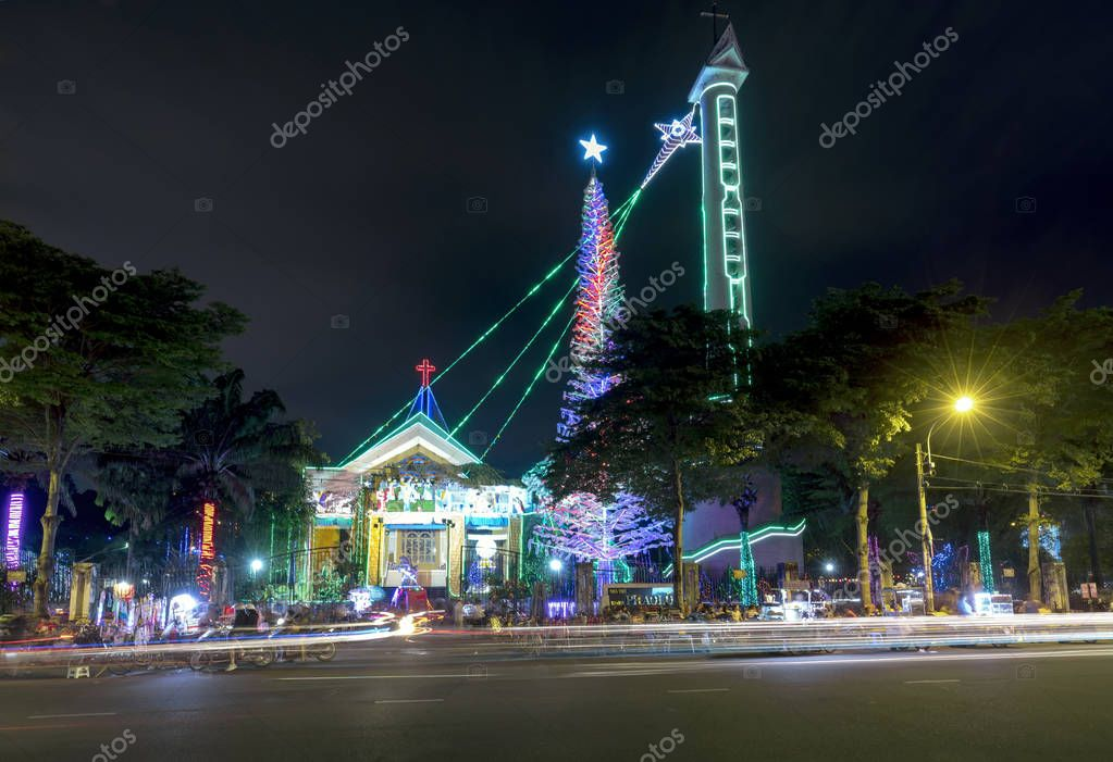 Ho Chi Minh City, Vietnam - December 27, 2017: Christmas tree lighting, cathedral belfry decorative shimmering nocturnal Christmases attract visitors to admire night scene in Ho Chi Minh City, Vienam
