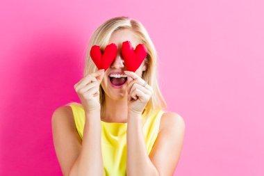 woman holding hearts cushions