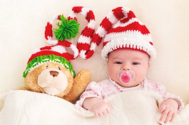 Baby in Christmas hat with teddy bear