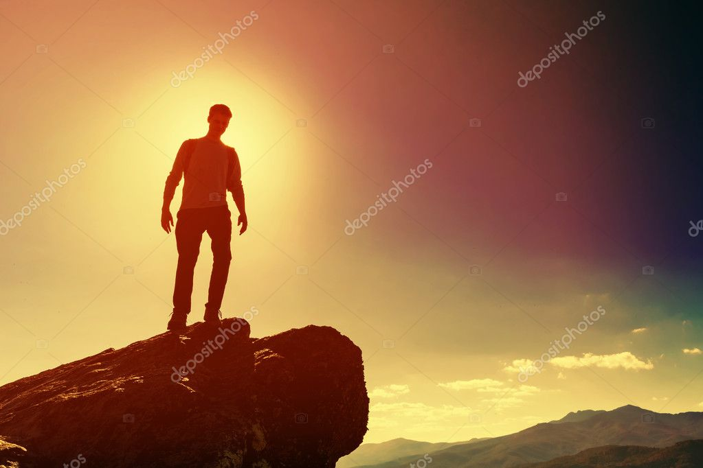 Man standing on edge of cliff
