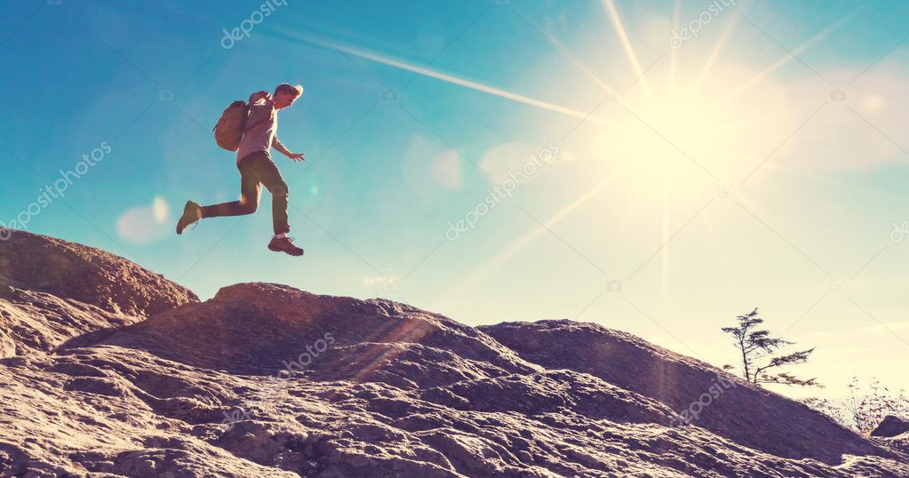 Man jumping over gap on mountain