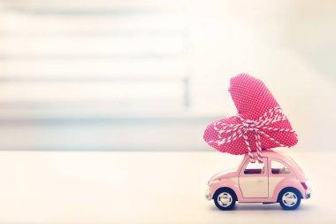 Miniature pink car carrying heart cushion