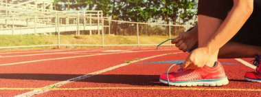Female jogger tying her shoes on a stadium track